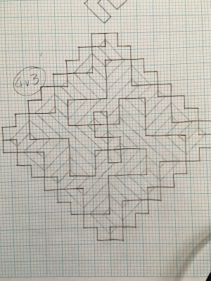 A spiral motif formed from intersecting diagonal lines, drawn in pencil on graph paper with horizontal and vertical mirror lines drawn in and surrounded by 4x4 boxes