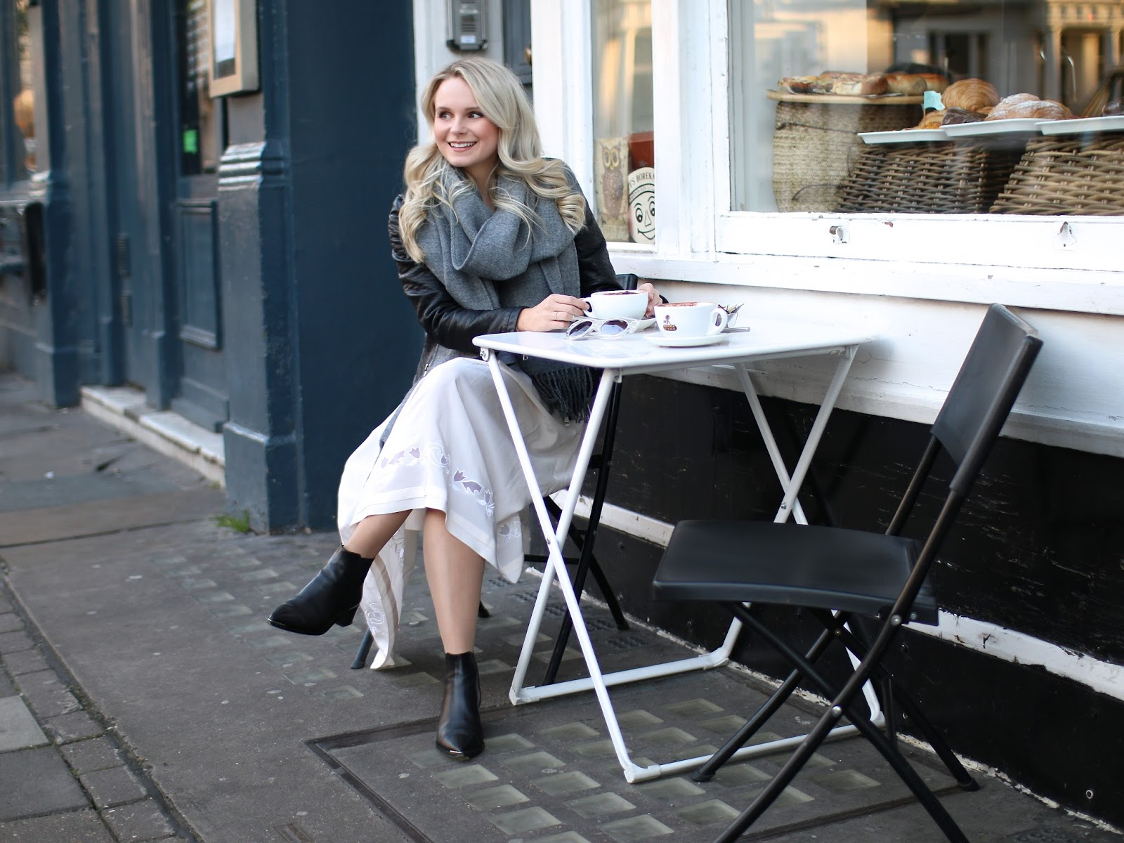 blogger in leather jacket in front of cute coffee shop in london