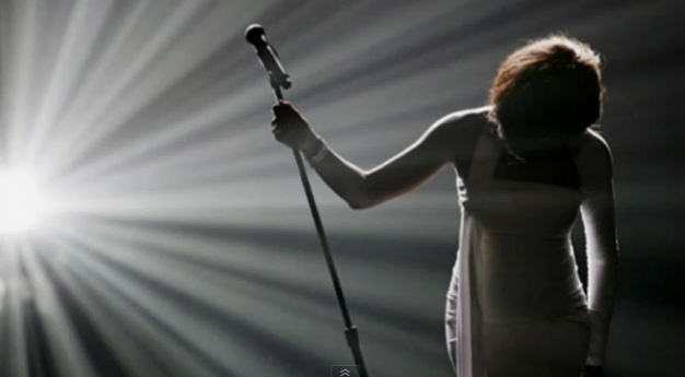 Whitney Houston bowing at microphone, backlit in shadow