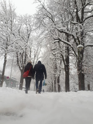 Couple strolling around snowy old town Innsbruck Austria