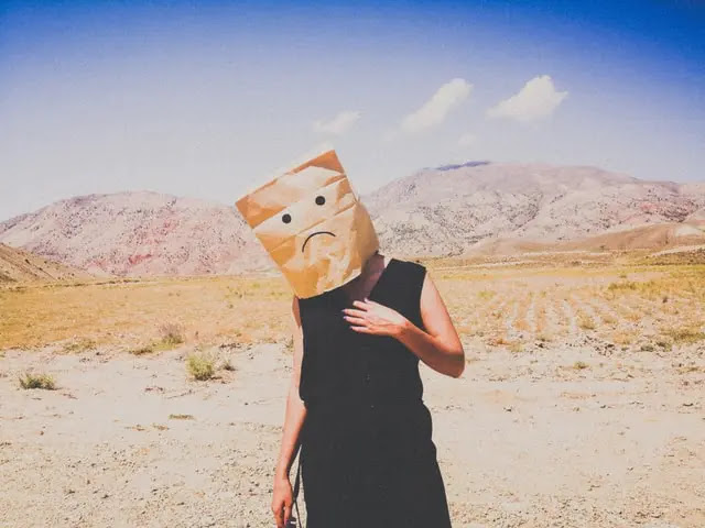 Persona con una bolsa de papel con un dibujo de cara triste tapando su cabeza