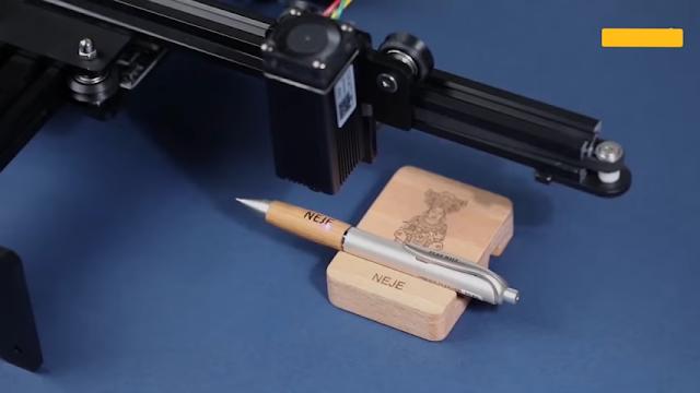 ماكينة تقوم بالطباعة على قلم خشبي