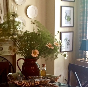 Pitcher of dill and daisies adorn the kitchen table in front of the fireplace.