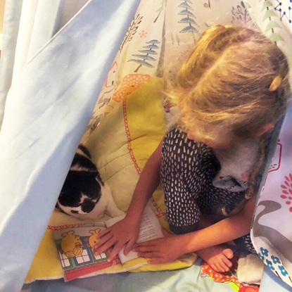 young blonde girl reading book with her black and white cat inside a tent