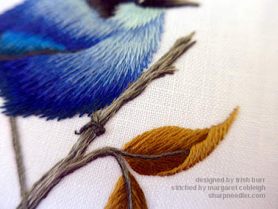 Thread painted blue bird and branch close-up