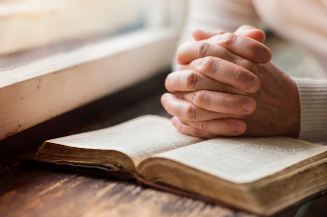 A folded hand on a bible praying