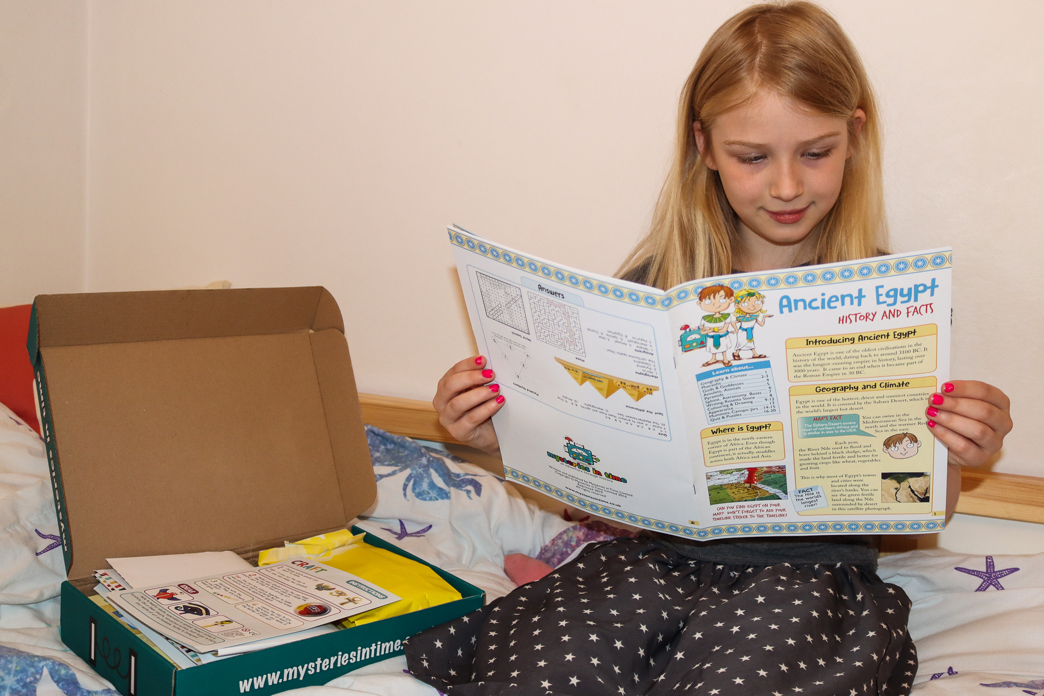 An 8 year old girl reading a magazine about ancient Egypt from the mysteries in time subscription box which is open next to her