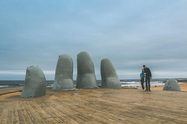 Casal em frente a uma escultura de dedos