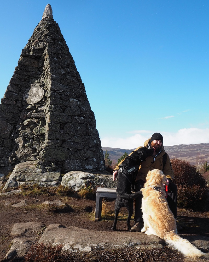 Gordon and dogs, on a bench by the Balmoral purchase cairn