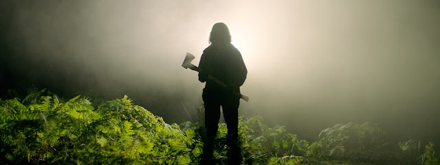 A man holding an axe stands in profile in the woods