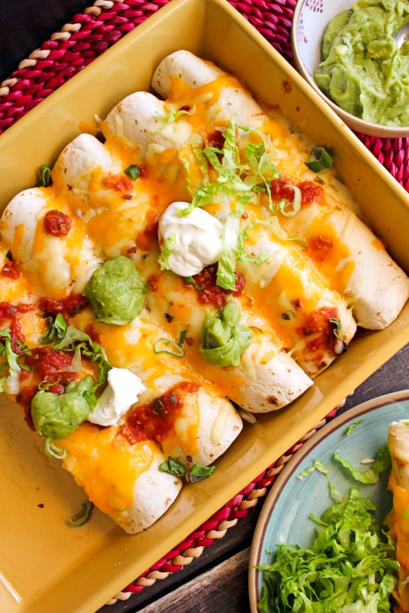 Top view of beef and bean burritos in a yellow casserole dish on a dark wood background.