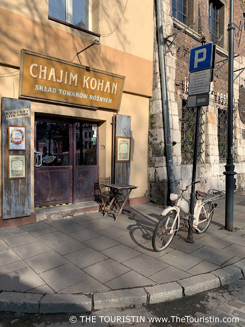 Cream coloured bicycle leaning against the post of a street sign. Opposite a wooden coffee house table in front of the entrance of a restaurant with the name over its glass door.