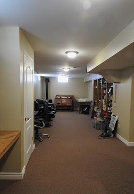 Long narrow basement room with shelving.