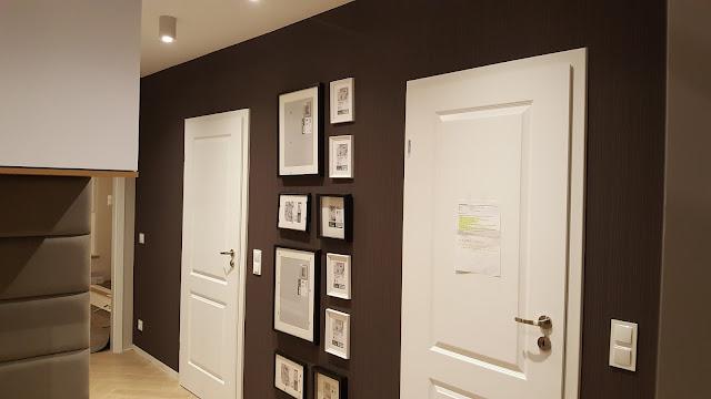 czarno-białe ramki na ścianie, białe drzwi w przedpokoju, białe drzwi do mieszkania