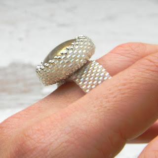 Серебристо-белое сверкающее кольцо со стеклянным кабошоном