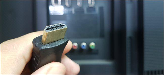 يد تمسك بكابل HDMI.