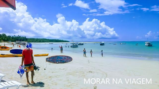 Praia tranquila, mar de água esverdeada e areia clara.
