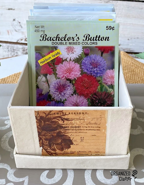 Painted box with rub on transfer holding seed packets.