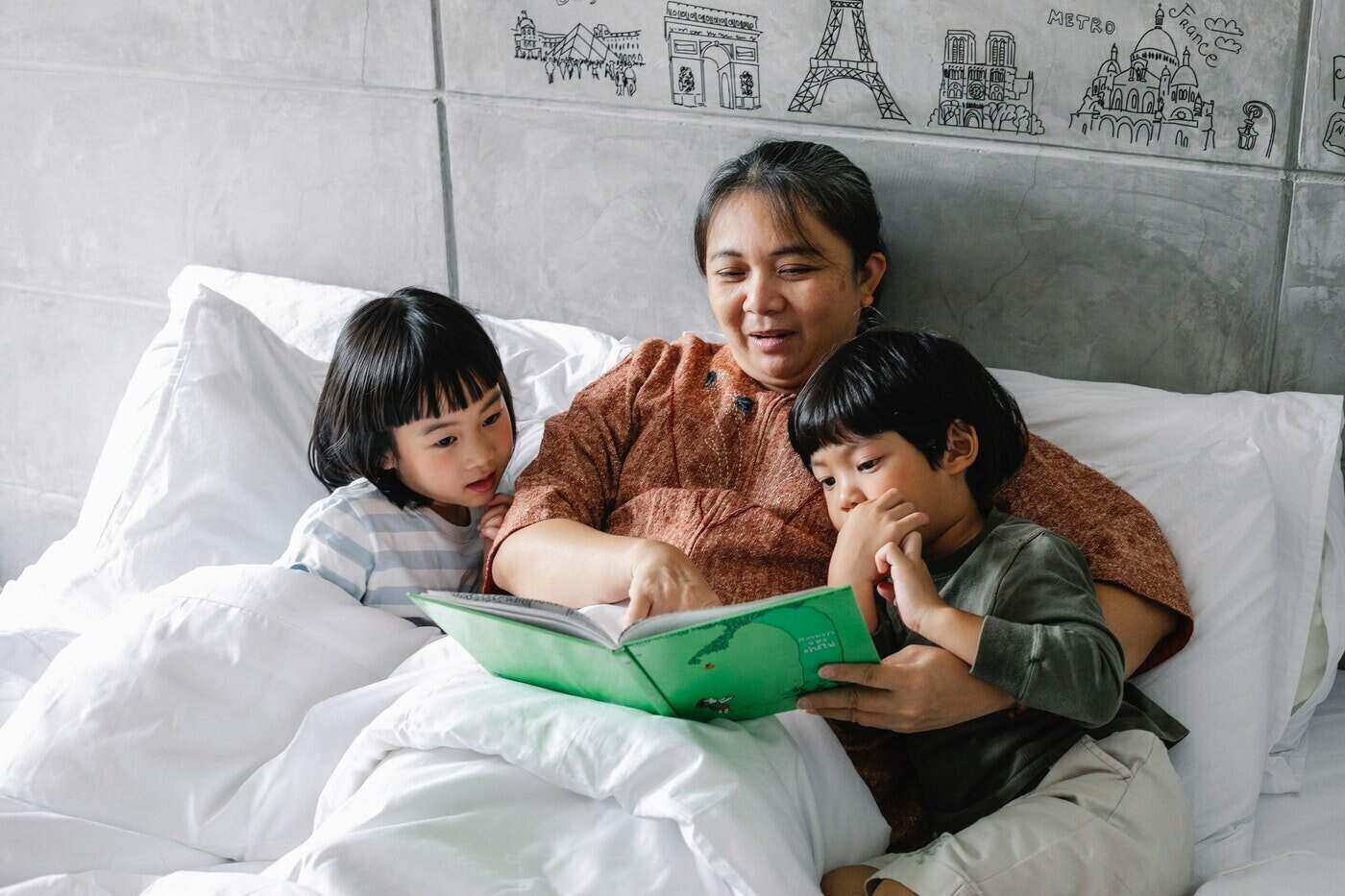 mother reading to two kids in bed - the work life balancing act