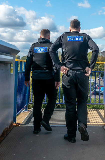 Two male British Transport Police officers on a bridge