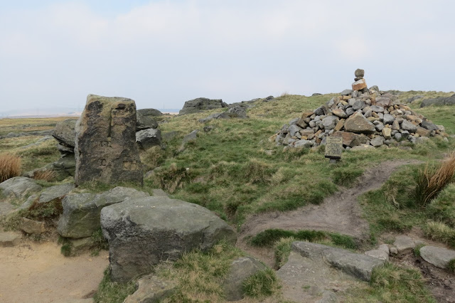 An old stone post on the left with carvings and a large stone cairn to the right.