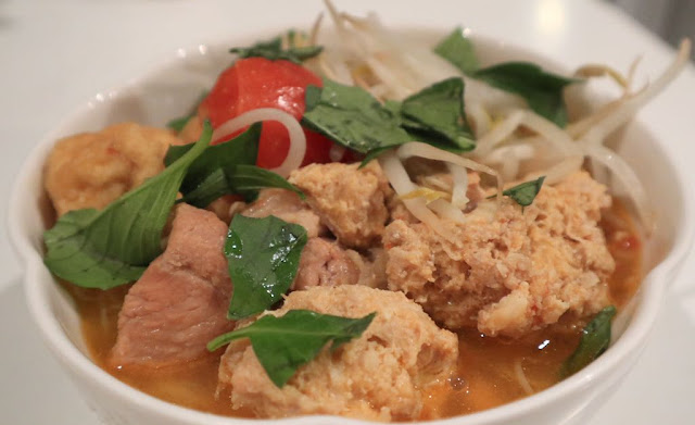 bowl of bun rieu soup (tomato, crab-pork-shrimp balls, pork short ribs, topped with thai basil in a white bowl
