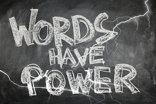 "A blackboard with ""Words have power"" written in large letters."