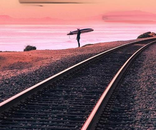 #PraCegoVer: Paisagem de entardecer, o sol avermelhado ilumina o mar mudando a cor das águas, uma linha férrea e ao longe um surfista com sua prancha.