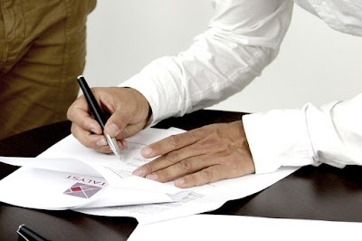 Un homme signe un contrat.