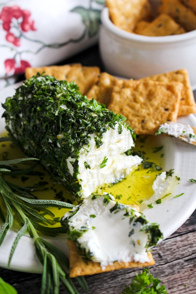 Side view of Herb and Olive Oil Goat Cheese Log on a cream colored plate with crackers next to it.