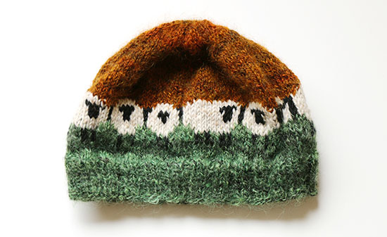 Hand knit wool hat with ivory and black sheep motif surrounded by dark orange above and green below on a white background.