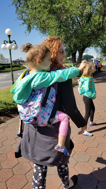 Curly red haired woman, with her back to the camera, is babywearing her toddler on her back in a purple, blue, and pink soft structured carrier.