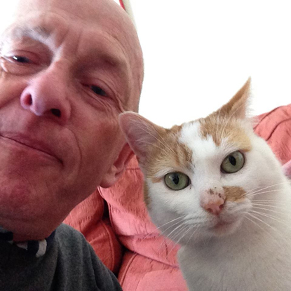 selfie of a man and his ginger and white cat