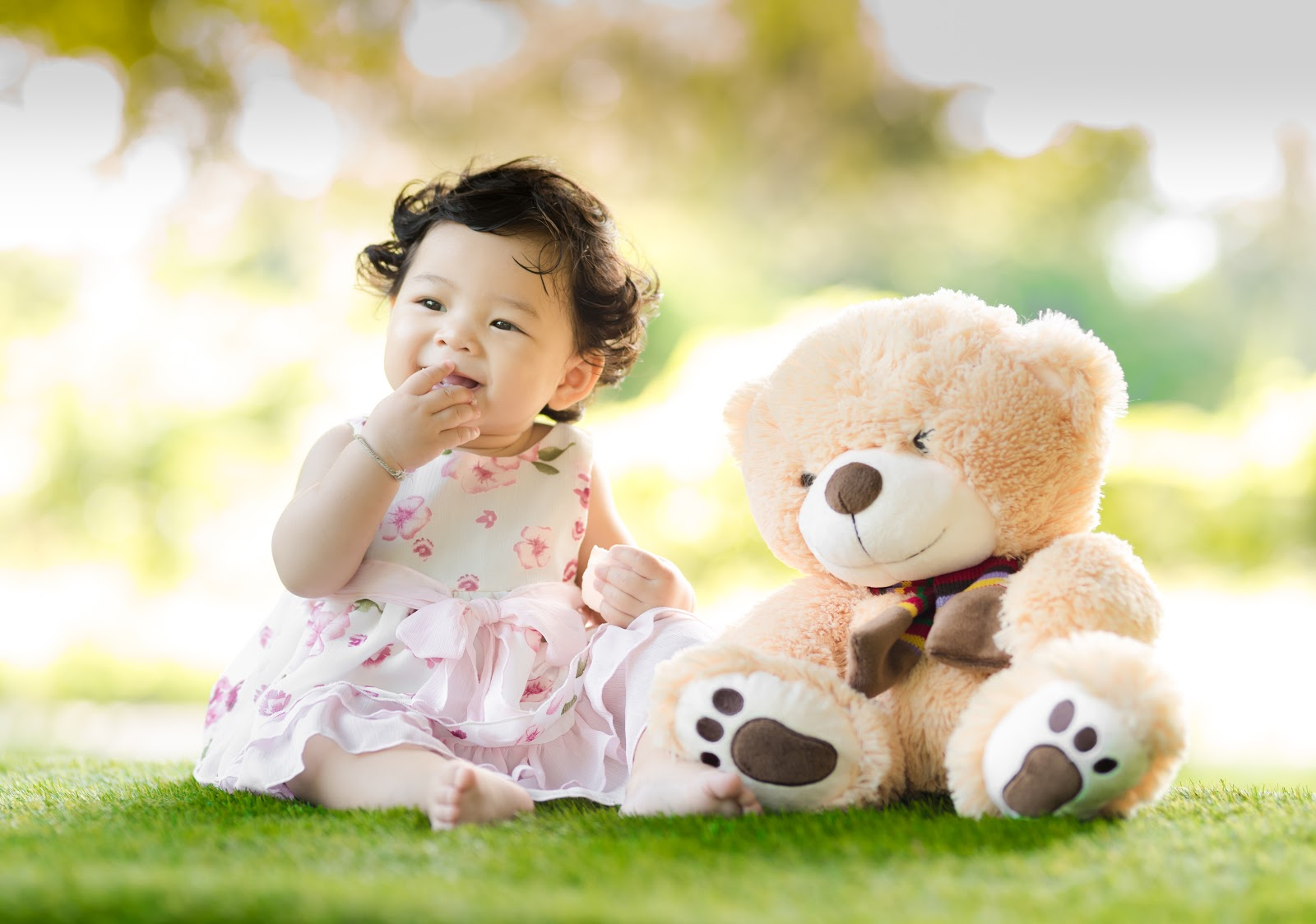 baby-sitting-on-green-grass-beside-bear-plush-toy-at-daytime-pictures