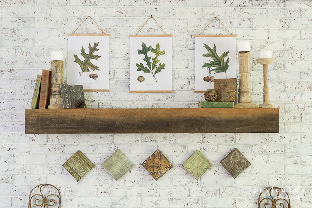 vintage leaf botanical prints and books with wooden candlesticks on a wood fireplace mantel