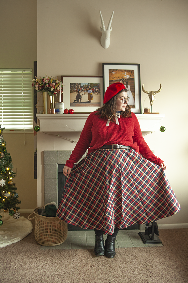 An outfit consisting of a red beret, navy blouse layered under a red skirt with a white ribbon tied into a bow under the collar, tucked into a red, blue and white plaid skirt and black Chelsea boots.