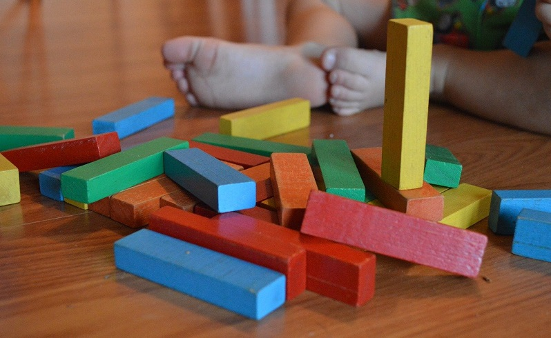 baby playing with coloured wooden blocks