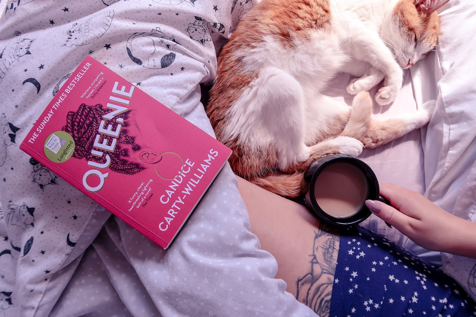 Birds eye view of Queenie by Candice Carty-Williams book, pink cover, on a bedsheet that is white with black cat outlines on it.