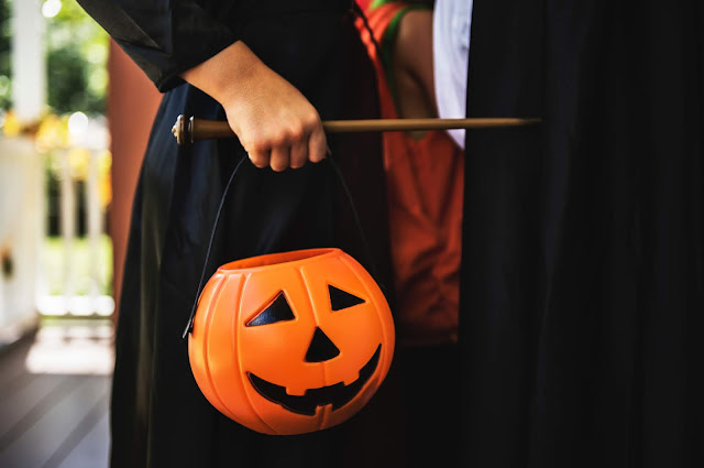 Middle shot of a child dressed in black, holding a pumpkin pail and a wand