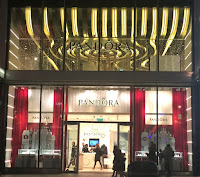 Pic of outside of Pandora's store in gold, silver and red.