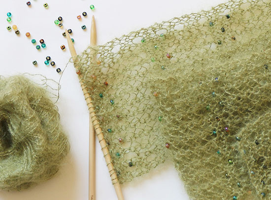 Beaded green hand knit scarf in progress on bamboo knitting needles next to a ball of yarn and extra beads on a white background.