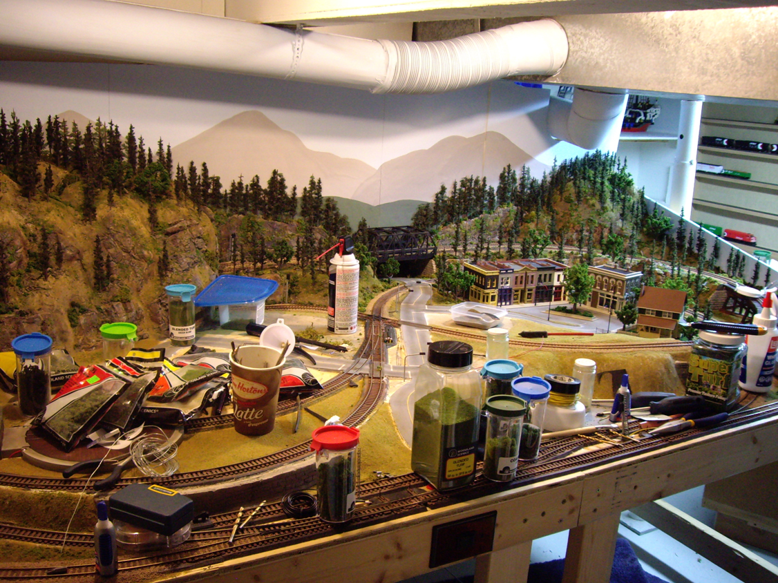 A partially finished 4 x 8 HO scale model railroad layout with various scenery construction materials