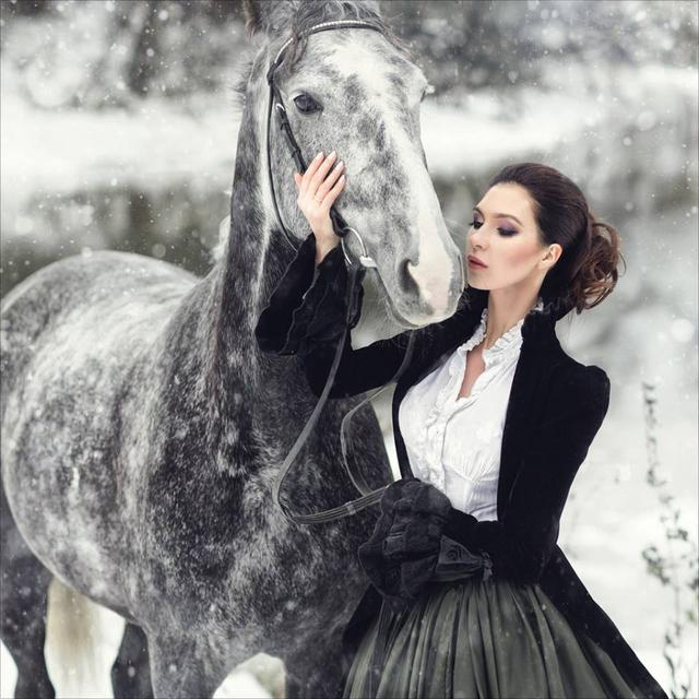 Woman wearing victorian clothing in the snow with her horse. Women's neo-victorian fashion and costumes.