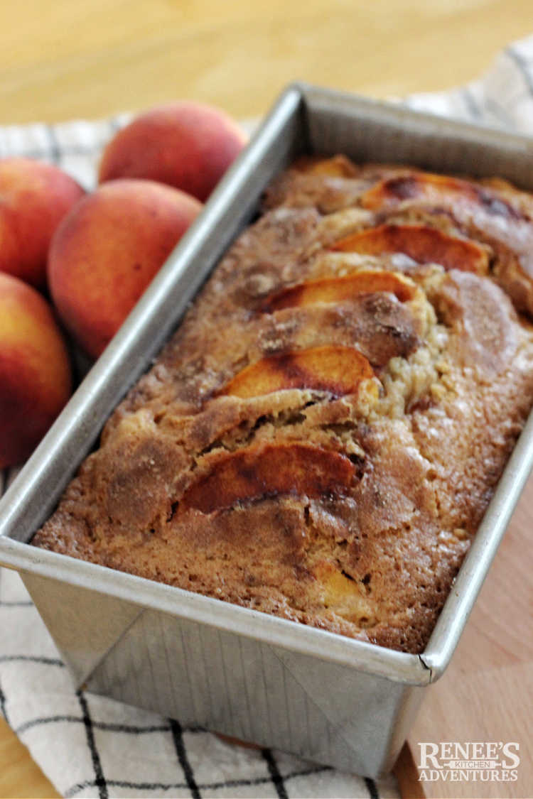 Peach bread in pan with peaches on the side
