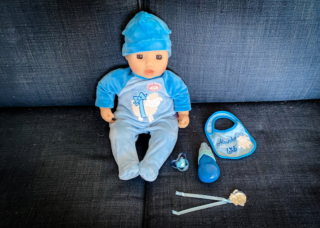 Baby Annabell Alexander sitting on the sofa with his accessories: a blue bib, bottle, dummy and pendant