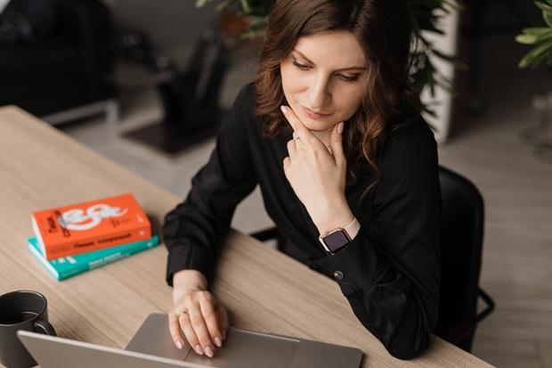 Mulher sentada à mesa mexendo em seu computador