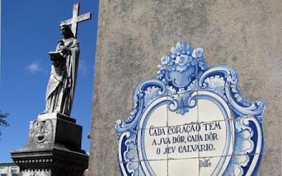 Escultura e azulejos com mensagem em um túmulo