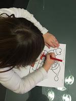 Enfant qui colorie son Père Noël pour la réalisation du coloriage magique