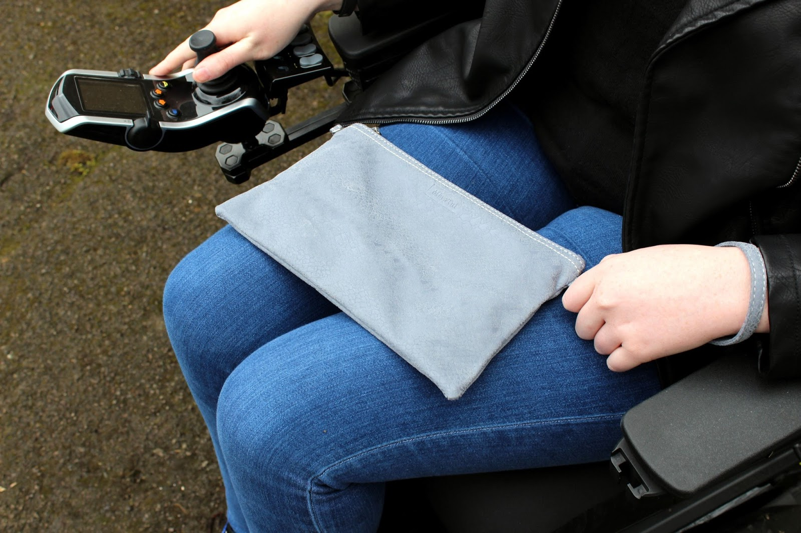 Shona is sitting in her powerchair, her lap is visible, she is holding a small grey clutch bag. Her powerchair controller and both hands are visible, one on the controller and the other holding the bag.