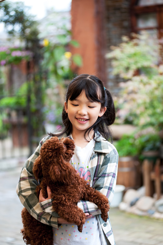 An Asian girl with a poodle in her arms, outside in the garden